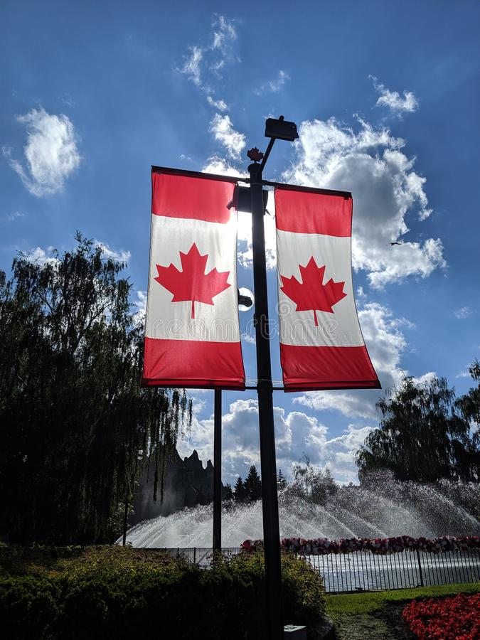 Banderas canadienses en el cielo de verano fotos de archivo