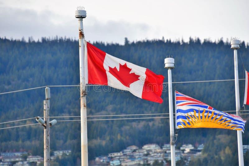Banderas colombinas canadienses y británicas que agitan orgulloso en el cielo imagen de archivo libre de regalías
