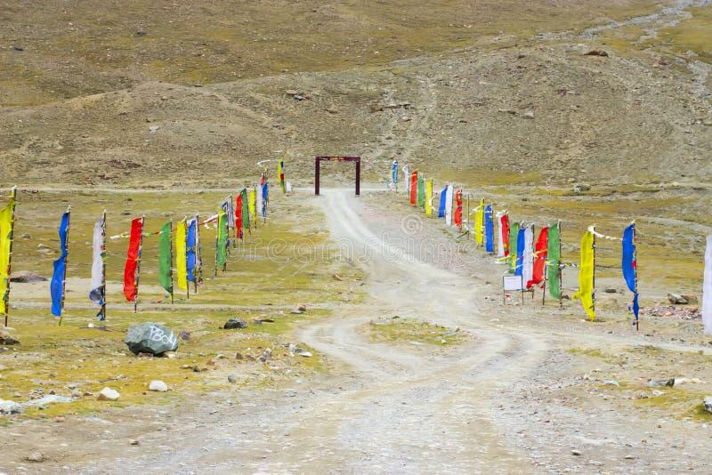 Banderas coloreadas tibetanas a lo largo del camino en montañas foto de archivo libre de regalías