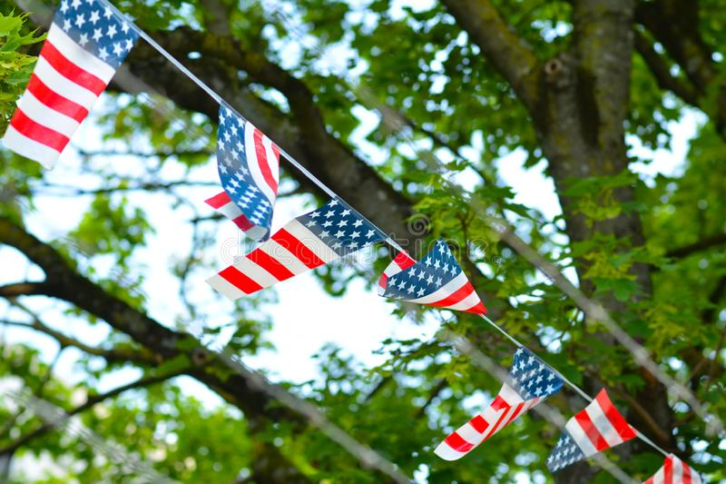 Banderas con colores americanos con las rayas rojas y las estrellas blancas en el fondo azul que cuelga en fila delante de la cer imagenes de archivo