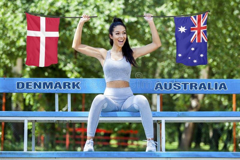 Banderas de Dinamarca y de Australia que son sostenidas por la muchacha atractiva hermosa fotos de archivo libres de regalías