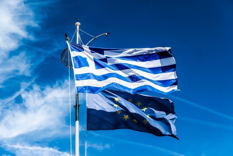 Banderas de Grecia y de la uni?n europea en el fondo del cielo azul, pol?tica de Europa fotografía de archivo