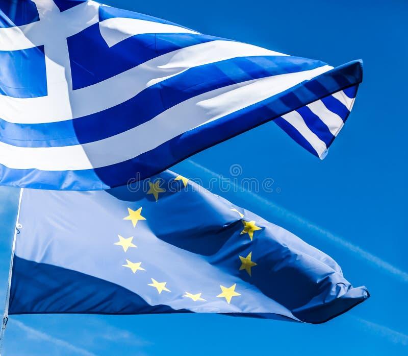 Banderas de Grecia y de la uni?n europea en el fondo del cielo azul, pol?tica de Europa fotografía de archivo libre de regalías