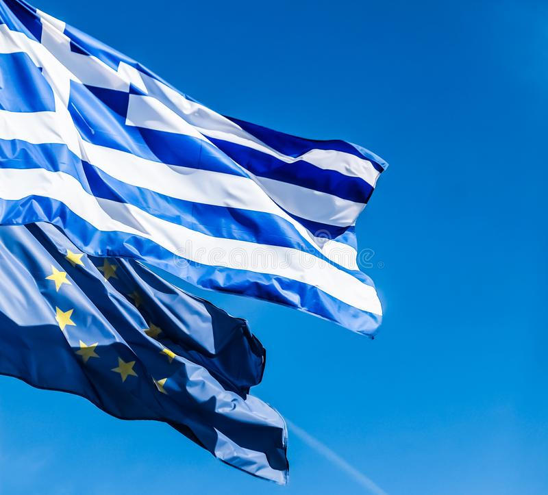 Banderas de Grecia y de la uni?n europea en el fondo del cielo azul, pol?tica de Europa foto de archivo