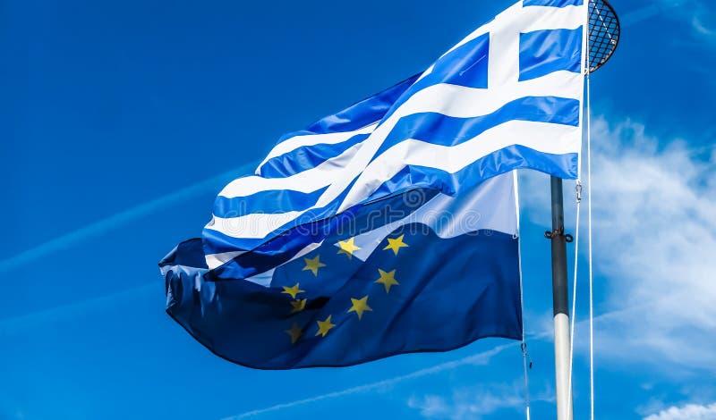 Banderas de Grecia y de la uni?n europea en el fondo del cielo azul, pol?tica de Europa foto de archivo libre de regalías