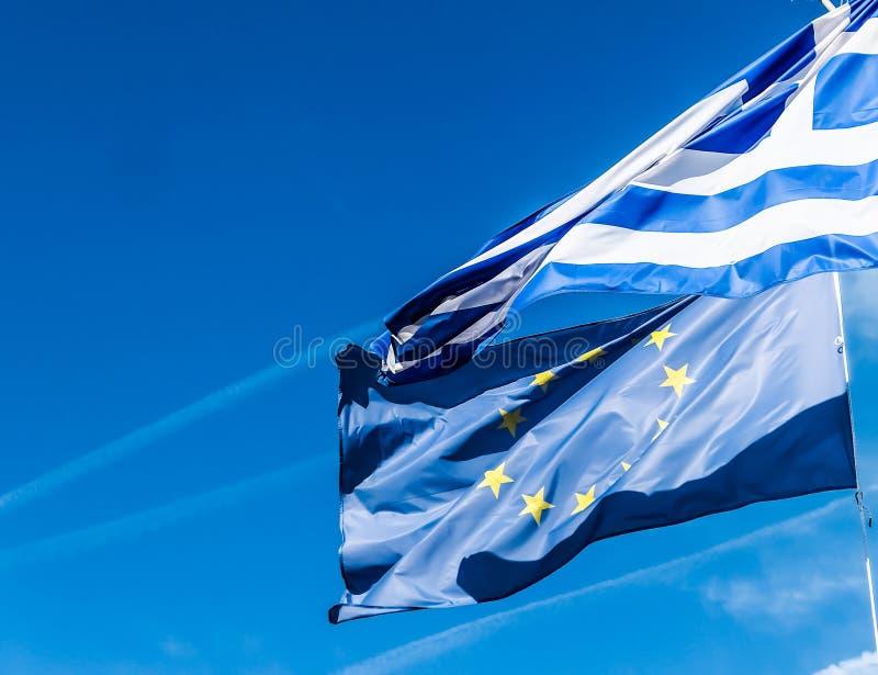 Banderas de Grecia y de la uni?n europea en el fondo del cielo azul, pol?tica de Europa imagen de archivo libre de regalías