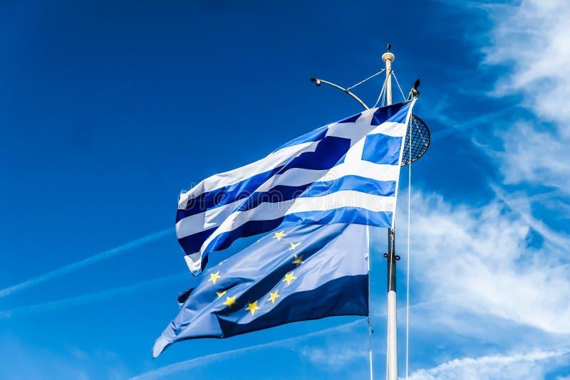 Banderas de Grecia y de la uni?n europea en el fondo del cielo azul, pol?tica de Europa imagen de archivo