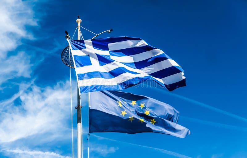 Banderas de Grecia y de la uni?n europea en el fondo del cielo azul, pol?tica de Europa fotos de archivo