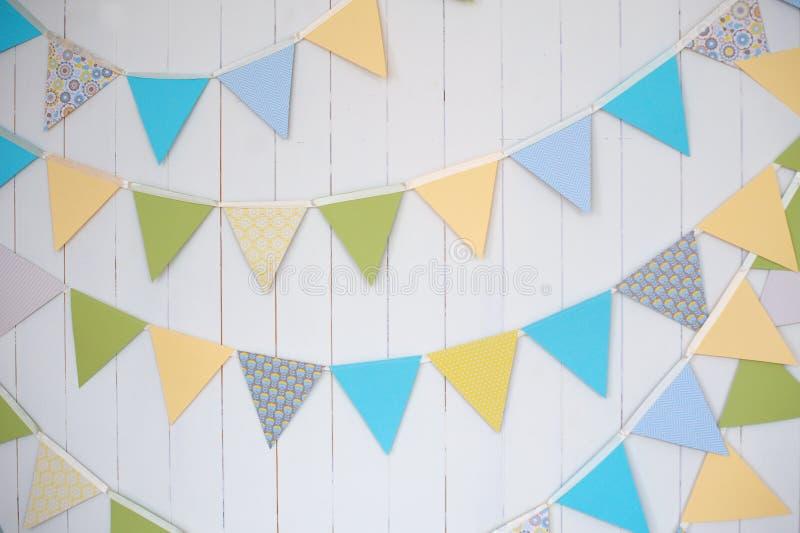 Banderas de la decoración del cumpleaños en un tiro blanco llano de la pared con la inclinación y el cambio fotos de archivo libres de regalías
