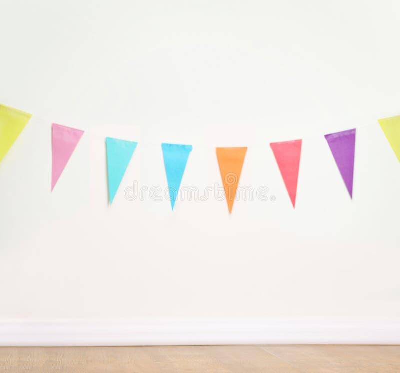 Banderas de la decoración del cumpleaños en una pared blanca llana fotografía de archivo
