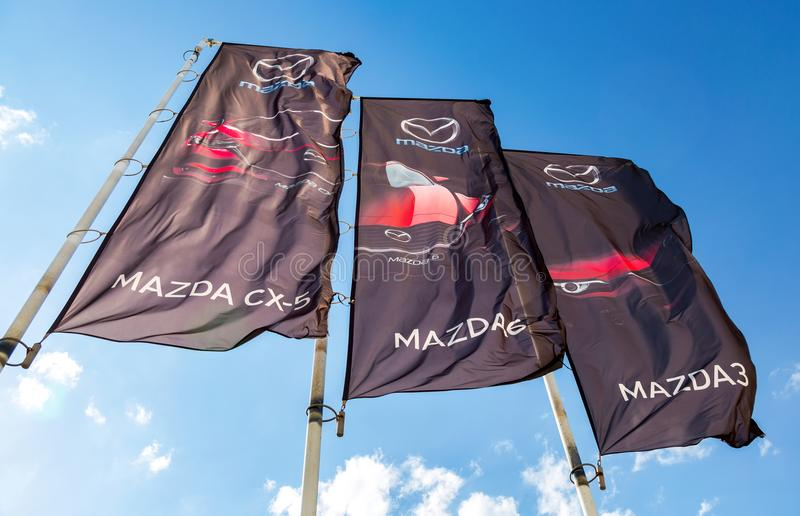 Banderas de la representación de Mazda sobre el cielo azul imagen de archivo libre de regalías