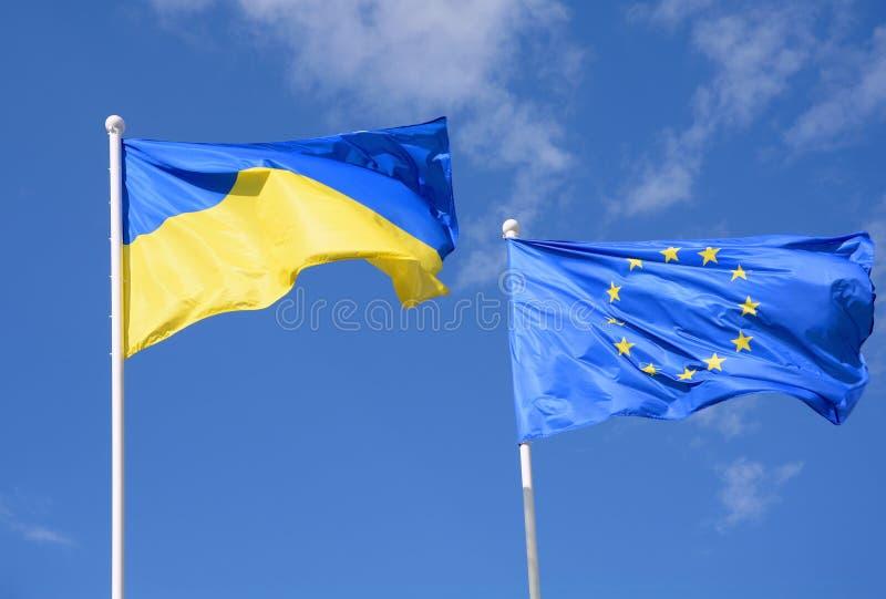 Banderas de la UE de Ucrania y de la unión europea contra el cielo azul imagen de archivo libre de regalías