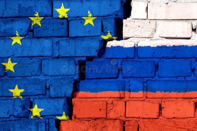 Banderas de la UE de la unión europea y de Rusia en la pared de ladrillo con la grieta grande en el centro stock de ilustración