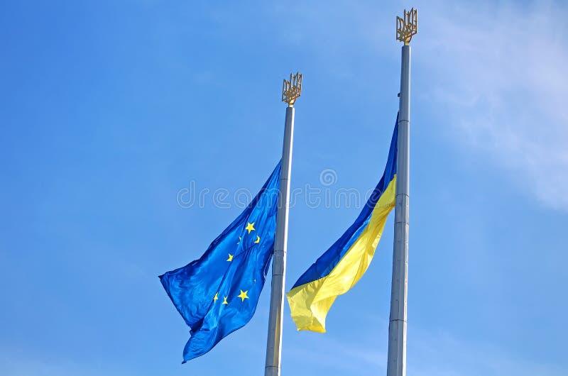 Banderas de la UE y de la Ucrania en la asta de bandera fotos de archivo