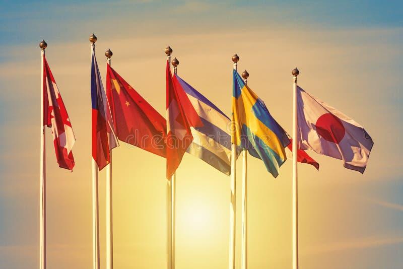 Banderas de los países diferentes contra una puesta del sol foto de archivo libre de regalías