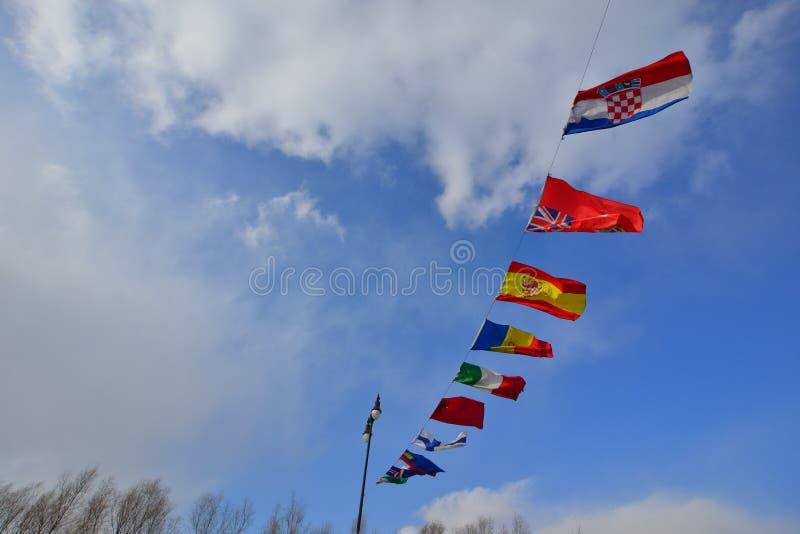 Banderas de los pa?ses diferentes que agitan en viento fotos de archivo