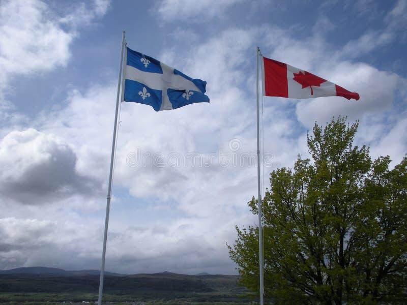 Banderas de Quebec y de Canadá que agitan en el viento foto de archivo