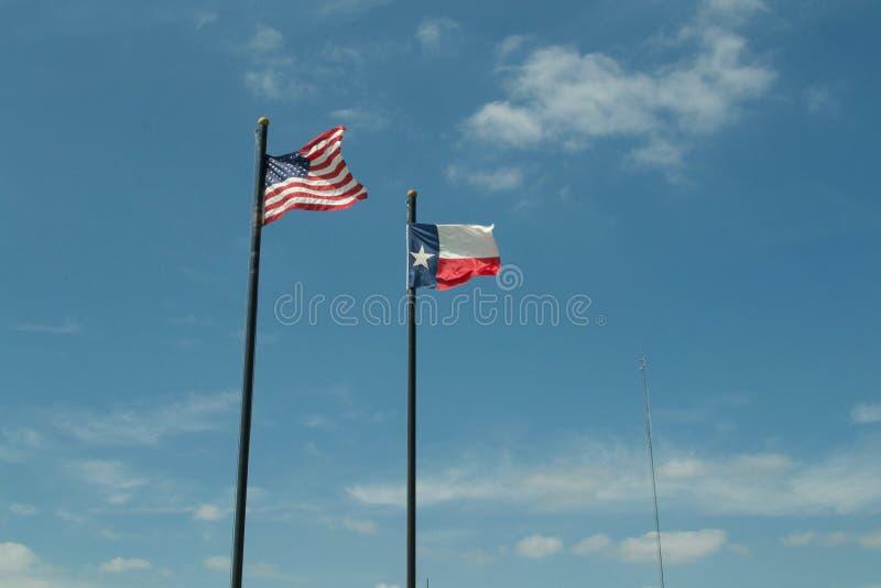 Banderas de Tejas y de Estados Unidos con el cielo azul y las nubes imagen de archivo libre de regalías