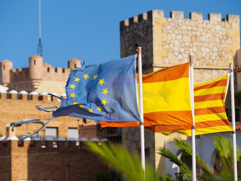 Banderas del español, del catalan y del europeo contra edificios de piedra viejos fotos de archivo
