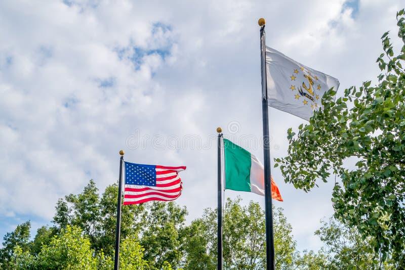 Banderas del estado de Estados Unidos, de Irland y de Rhode Island que agita contra el cielo azul, cerca del monumento irlandés d imágenes de archivo libres de regalías