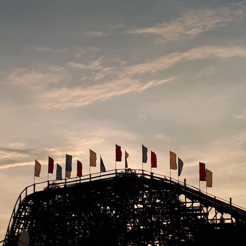 Banderas del roller coaster en la puesta del sol fotografía de archivo libre de regalías