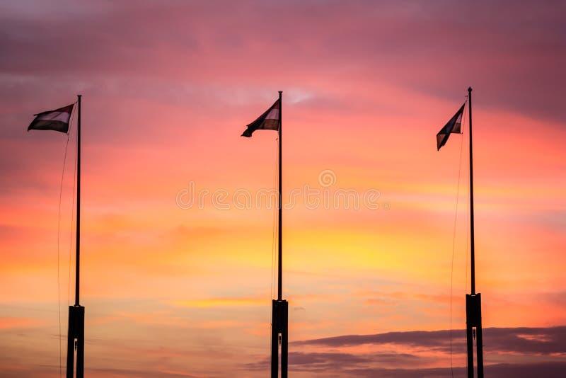 Banderas en puesta del sol imagenes de archivo