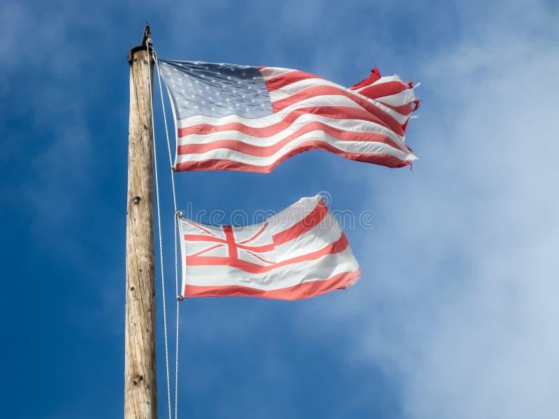 Banderas hawaianas y americanas descoloradas y gastadas en una asta de bandera de madera foto de archivo