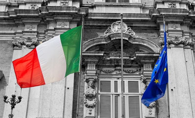 Banderas italianas y europeas en un balcón de la academia italiana del ejército que agita en el viento imagen de archivo libre de regalías
