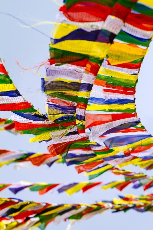 Banderas tibetanas budistas del rezo contra el cielo azul imagenes de archivo