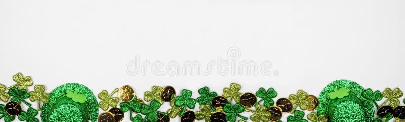 Banderoll på St Patricks Day mot en vit bakgrund, ovanifrån med guldmynt, schampo- och leprechaun-hattar arkivfoton
