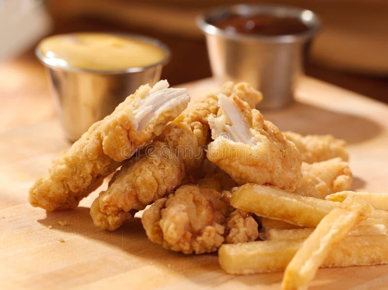 Bandes de poulet frit avec les pommes frites et la sauce. photos stock