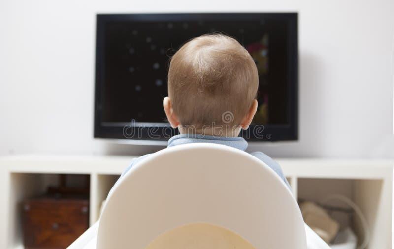 Bandes dessinées de observation de bébé garçon à la TV image stock