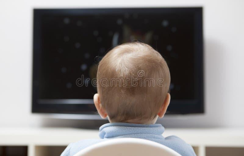 Bandes dessinées de observation de bébé garçon à la TV images stock