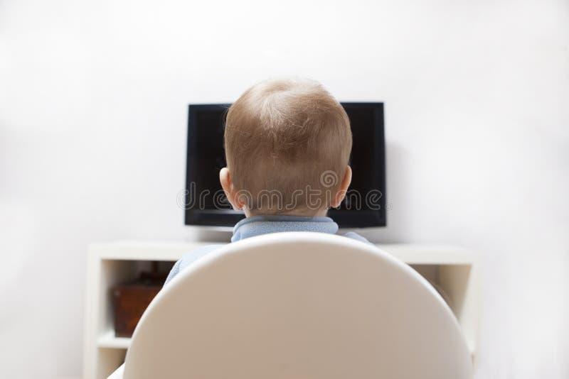 Bandes dessinées de observation de bébé garçon à la TV photos stock