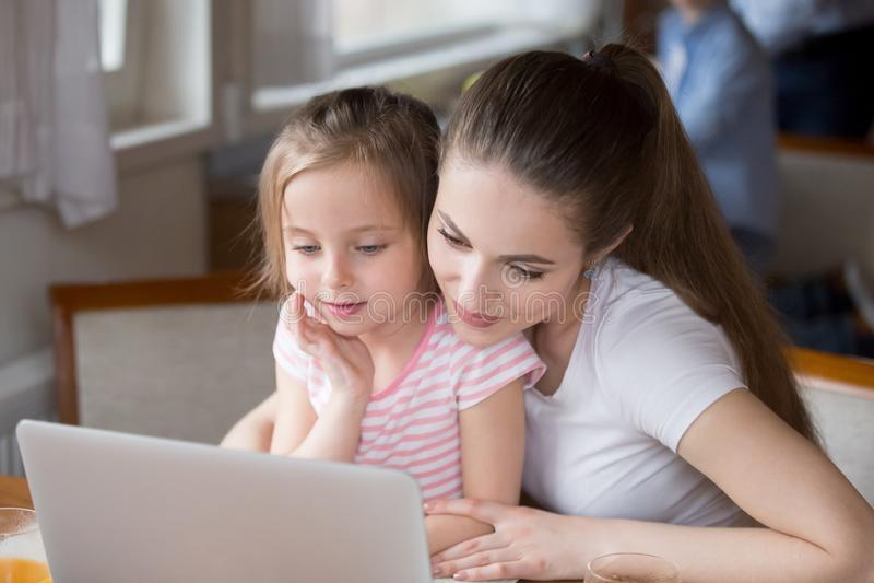 Bandes dessinées de observation de maman affectueuse avec la fille à l'ordinateur portable photo stock