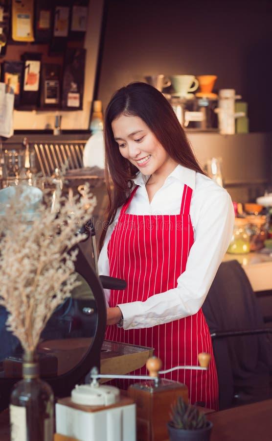 Bandes rouges de tablier d'usage femelle asiatique de barman avec des valeurs maximales de concentration au poste de travail de s photo stock