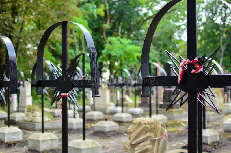 Bandet med nationella färger av Polen band upp till det gamla korset på kyrkogården Allt helgondagbegrepp arkivbilder