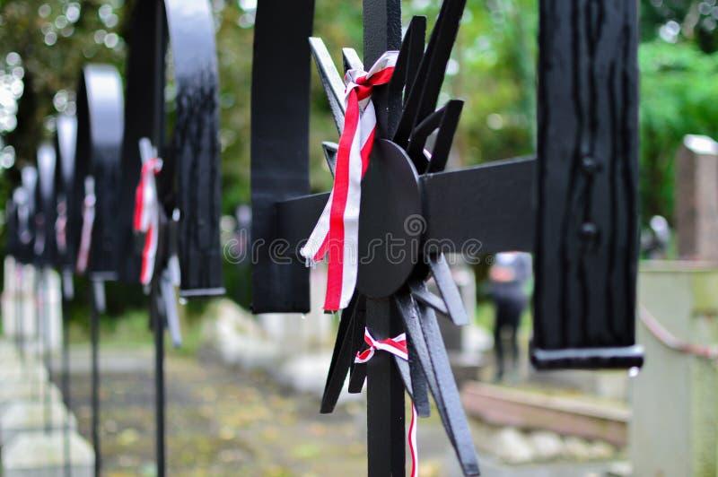 Bandet med nationella färger av Polen band upp till det gamla korset på kyrkogården Historiebegrepp royaltyfria foton