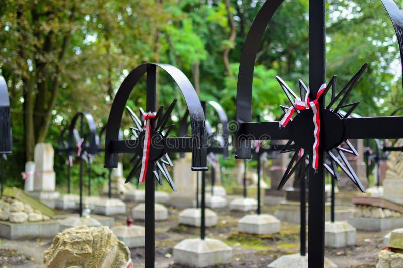 Bandet med nationella färger av Polen band upp till det gamla korset på kyrkogården Rebelion upprorbegrepp fotografering för bildbyråer