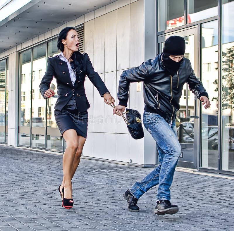 Bandido que roba el bolso imagen de archivo