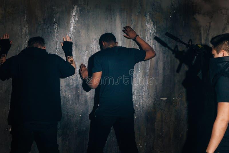 Bandidos arrestados cerca de la pared en la noche foto de archivo libre de regalías