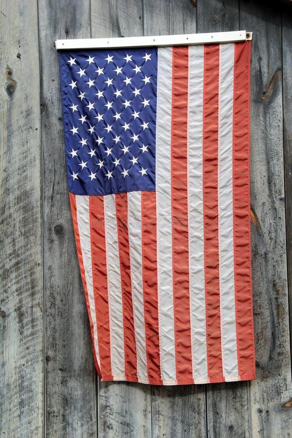 Bandiera americana che appende sul legno grigio del granaio fotografie stock libere da diritti
