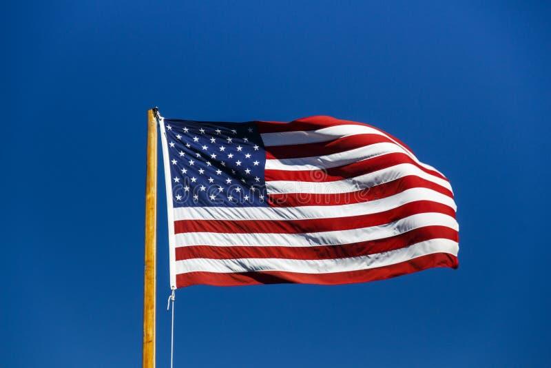 Bandiera americana che fluttua in cielo blu, U.S.A., 2015 immagini stock