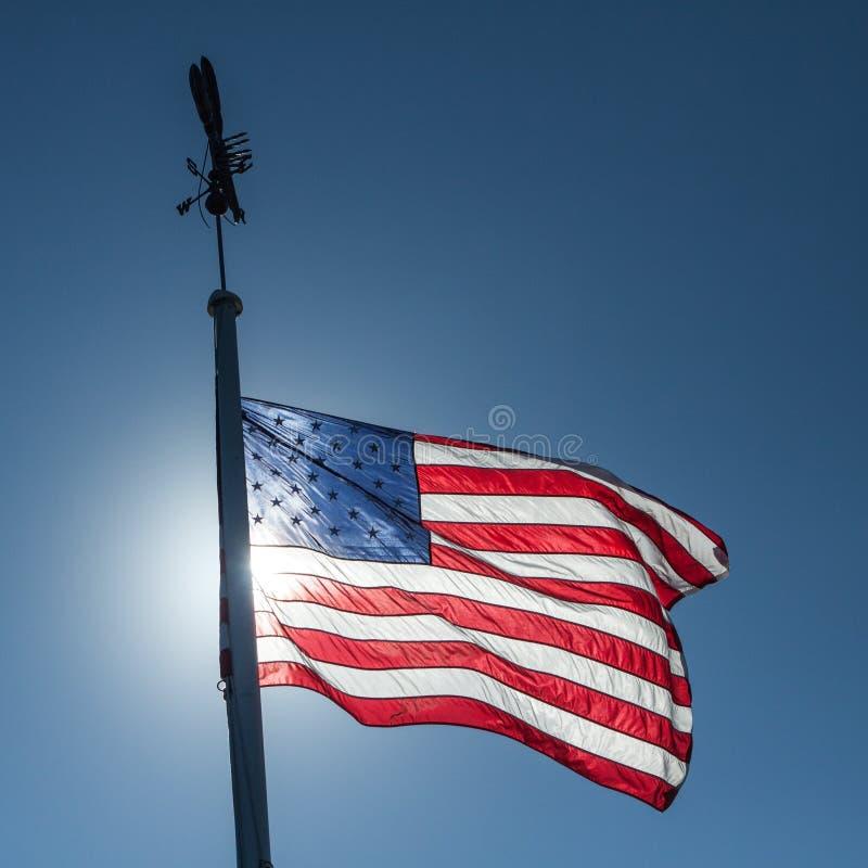 Bandiera americana che fluttua nel cielo blu fotografia stock libera da diritti