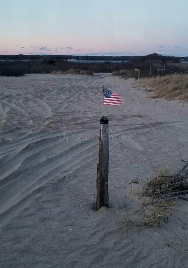 Bandiera americana che ondeggia nel vento sulla spiaggia immagini stock