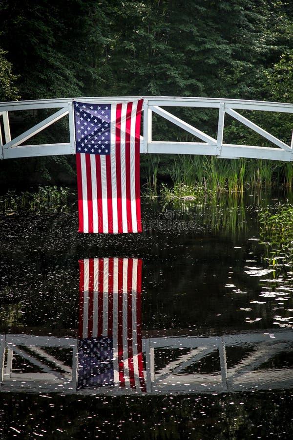 Bandiera americana che pende dal ponte di legno con la riflessione in acqua fotografia stock libera da diritti