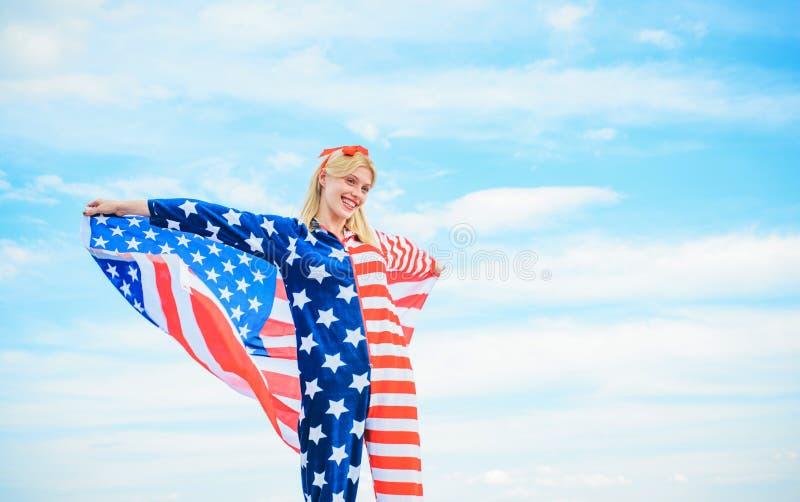 Bandiera americana della tenuta della giovane donna sul fondo del cielo blu, durante in costume rosso, bianco e blu, celebrare un immagini stock
