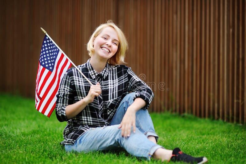 Bandiera americana felice della tenuta della giovane donna immagine stock libera da diritti