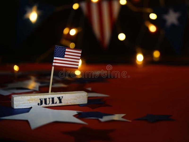 Bandiera americana increspata e calendario di legno del cubo con il quarto luglio, data di festa dell'indipendenza di U.S.A., fon immagine stock libera da diritti