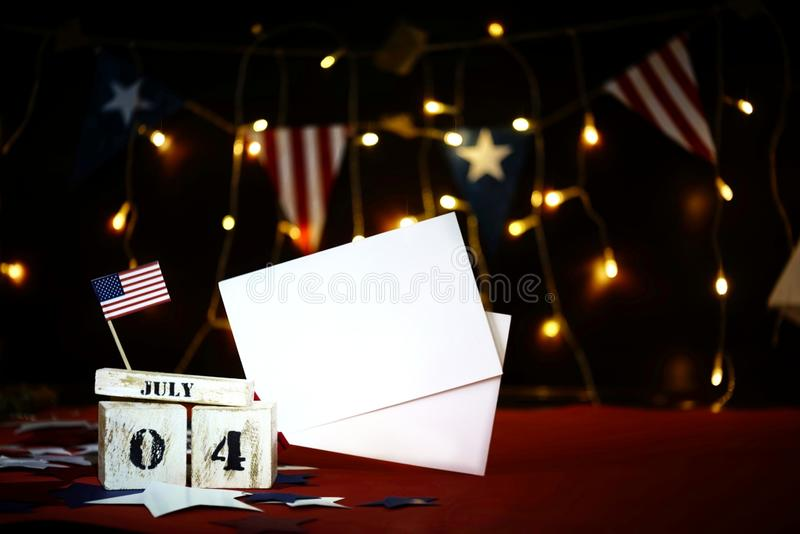 Bandiera americana increspata e calendario di legno del cubo con il quarto luglio, data di festa dell'indipendenza di U.S.A., fon immagini stock